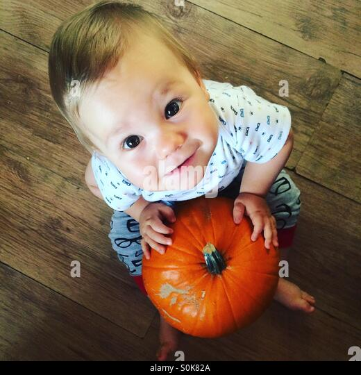 Photo from above of a 8 months old baby boy,  joyfully looking into the camera, sitting on a wooden kitchen floor, - Stock Image