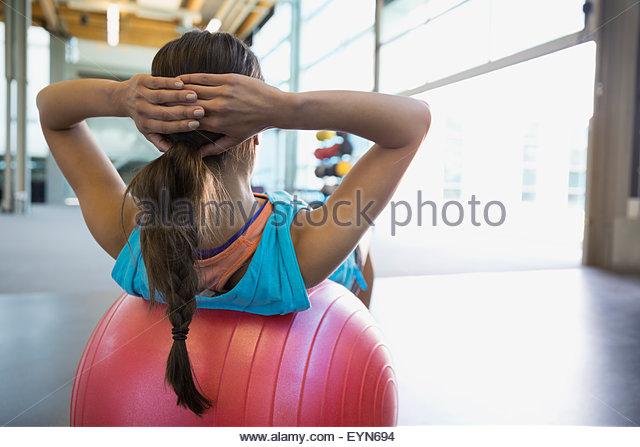 Woman doing fitness ball sit-ups at gym - Stock Image