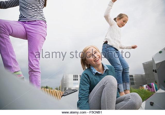 Portrait smiling girl having fun at playground - Stock Image