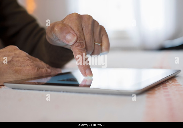 Female mature writing digital tablet indoors closeup - Stock Image