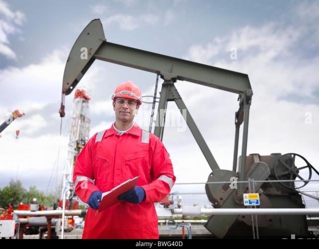 Worker in front of oil well pump - Stock-Bilder