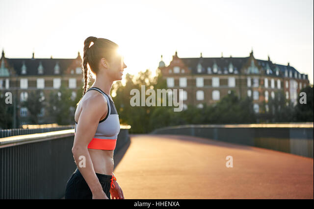 Female runner practicing on empty road as sun pokes out from behind apartment houses - Stock Image