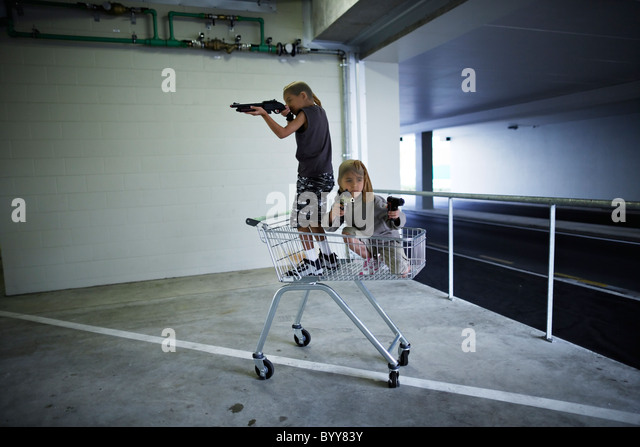 Children with stocking masks and toy guns in underground carpark prepare for big hold-up. - Stock Image