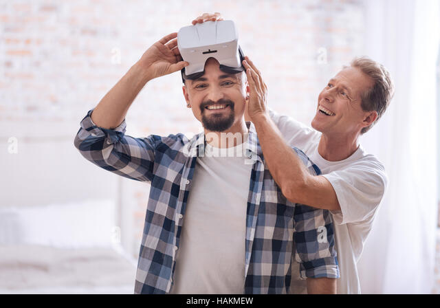 Delighted homosexual couple testing the virtual reality glasses at home - Stock-Bilder
