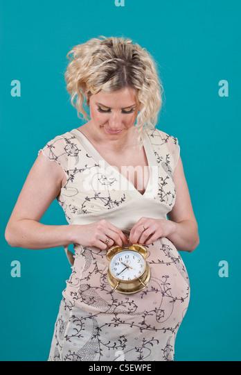 Pregnant woman holding alarm clock - Stock Image
