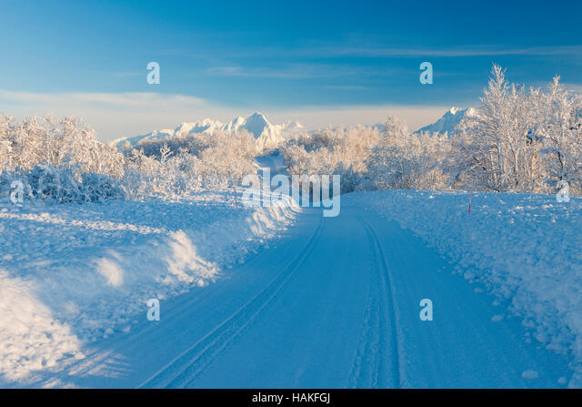 Snowy Road with Mountains in Winter, Breivikeidet, Troms, Norway - Stock Image