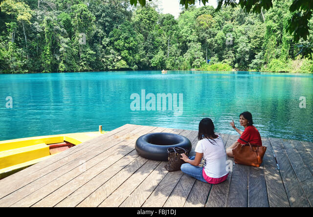 Two women relaxing and chatting by Labuan Cermin Lake - Stock Image
