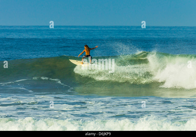 Surfer riding a wave at popular Playa Guiones surf beach, Nosara, Nicoya Peninsula, Guanacaste Province, Costa Rica - Stock-Bilder
