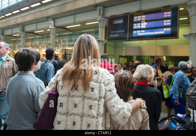 London , St Pancras Station , back rear view of family mother boys waiting at gate by train arrivals information - Stock-Bilder