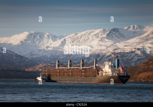 Panamanian ship Hanjin Marugame, assisted by a tug boat, departs Womens Bay, Kodiak Island, Southwest Alaska, Autumn - Stock Image