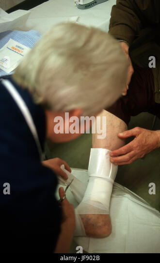 District nurse on a home visit dressing a persons leg ulcers - Stock Image