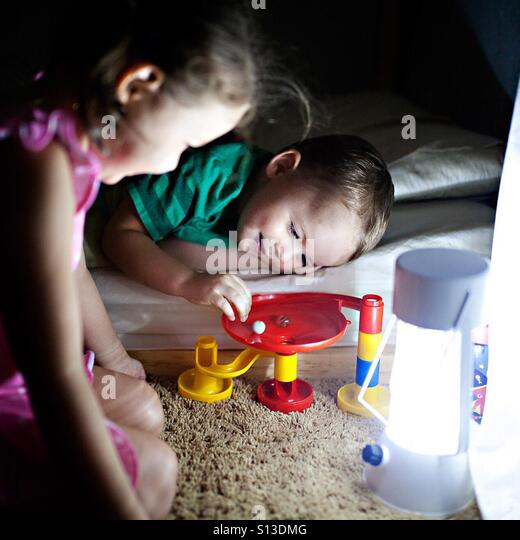 Toddler and your girl play with a marble run toy at bedtime by lamp light - Stock Image