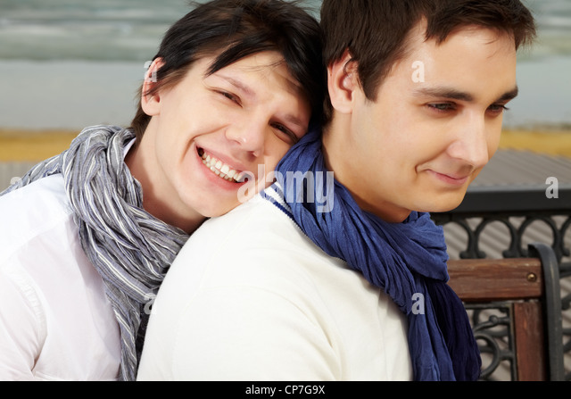 Portrait of smiling homosexual lovers dressed in elegant casual spending time outdoors - Stock-Bilder