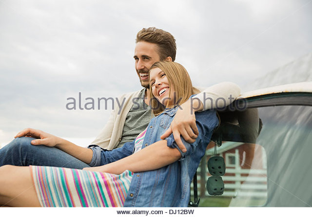 Affectionate couple sitting on vintage pick-up truck - Stock-Bilder