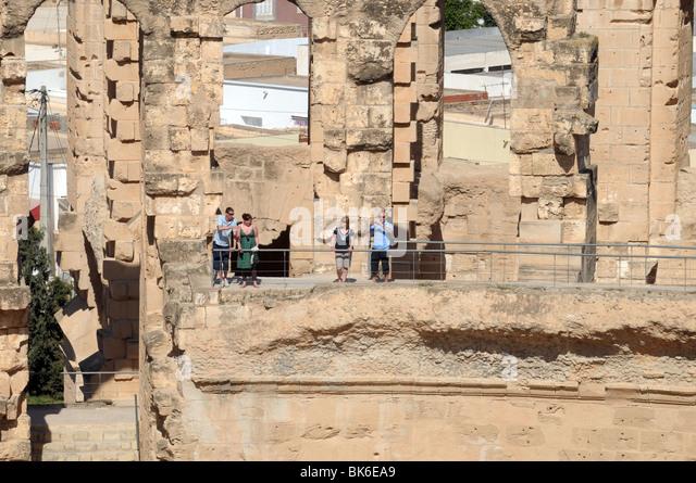 Tourists inside El Jem Roman Amphitheatre, Tunisia. - Stock Image