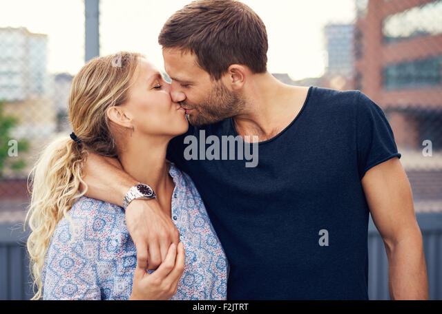 Amorous attractive young couple enjoy a romantic kiss as they stand arm in arm outdoors in an urban street - Stock-Bilder