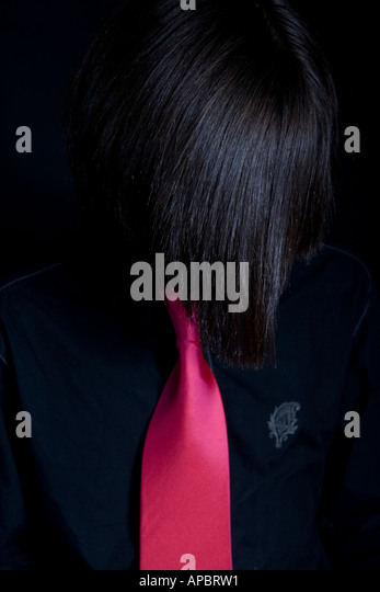 Fashion pop style image of a young male with shiny hair and long fringe in pink tie and black shirt - Stock-Bilder