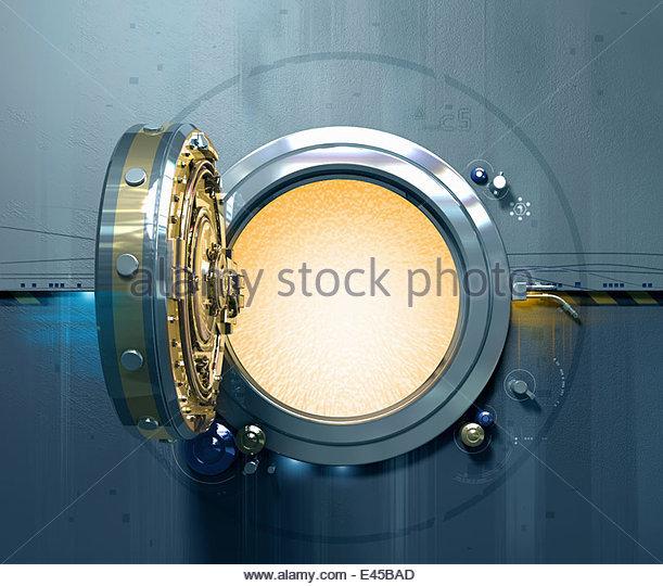 Open vault door with glowing light inside - Stock Image