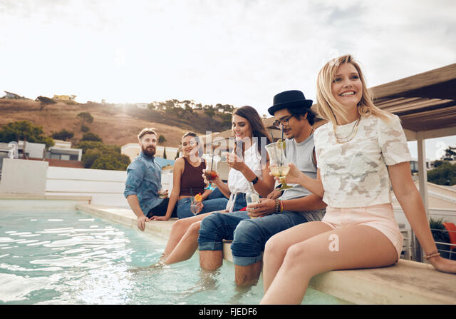 Multi-ethnic group of young people hanging out by swimming pool holding cocktails. Happy friends enjoying party - Stock Image