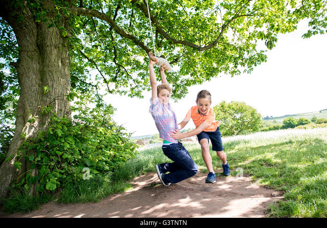 Two boys playing on a swing in the countryside. - Stock Image