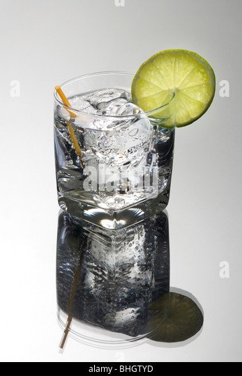 Club soda or Gin or Vodka and tonic mixed drink with lime slice garnish on a grey background - Stock Image
