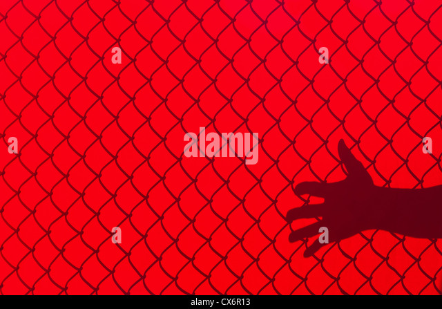 Red Fence and hand Shadow, concept of freedom - Stock-Bilder
