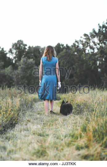 Vintage teen and her Pomeranian dog walking away in a field - Stock Image