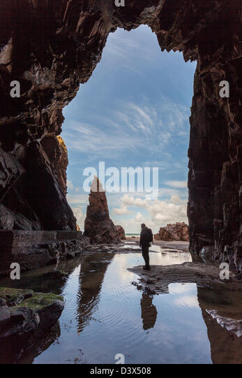 Needle Rock with person standing in Plemont Cave, Jersey, Channel Islands, UK - Stock Image