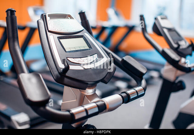 Aerobics spinning exercise bikes gym room with many in a row - Stock-Bilder
