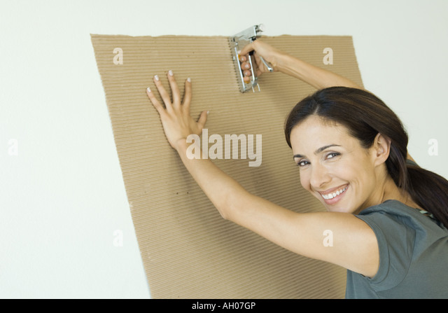 Woman stapling corrugated cardboard to wall - Stock Image