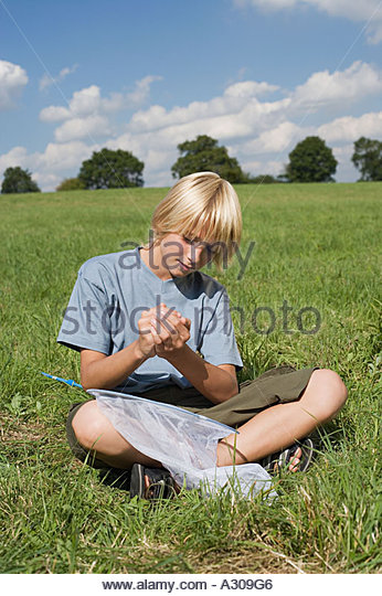 Boy holding a butterfly - Stock Image