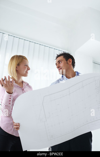two architects examining blueprint indoors. Copy space - Stock Image