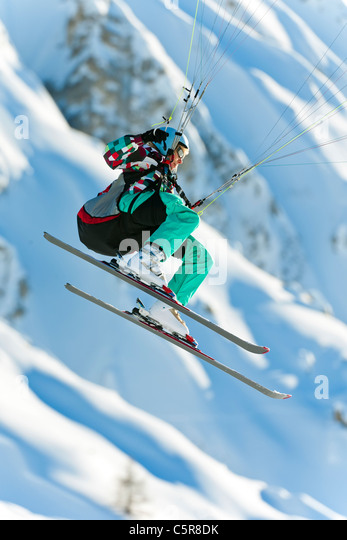 A Paraglider pilot flying her wing past snowy mountains. - Stock-Bilder