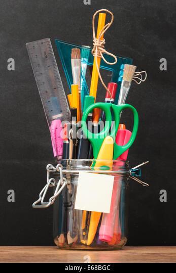 School accessories in jar on desktop with blackboard in the background - Stock Image