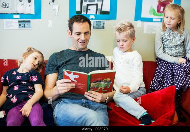 Male teacher reading story book for children in kindergarten - Stock Image