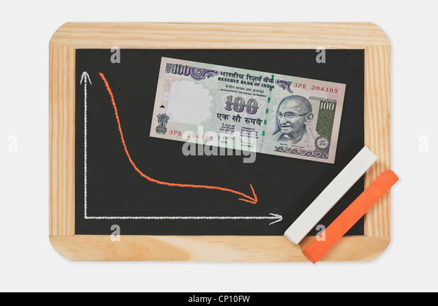Chart with an declined curve. On the chalkboard lies a 100 rupee bill with the portrait of Mahatma Gandhi. - Stock-Bilder