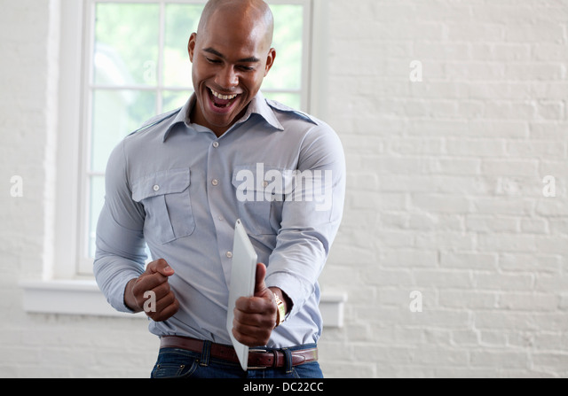 Mid adult office worker holding digital tablet and punching air - Stock Image