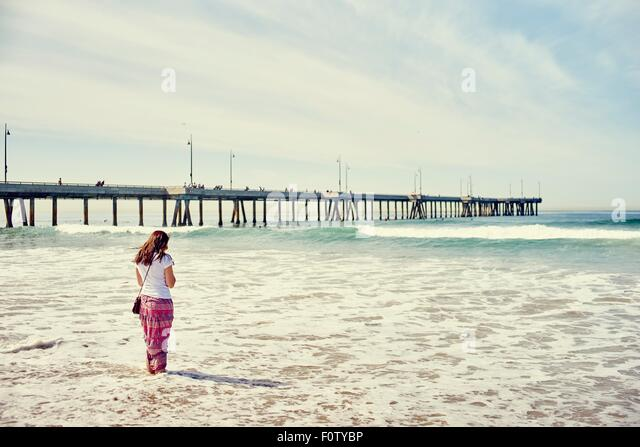 Rear view of woman paddling in front of pier, Venice Beach, Los Angeles, California - Stock-Bilder