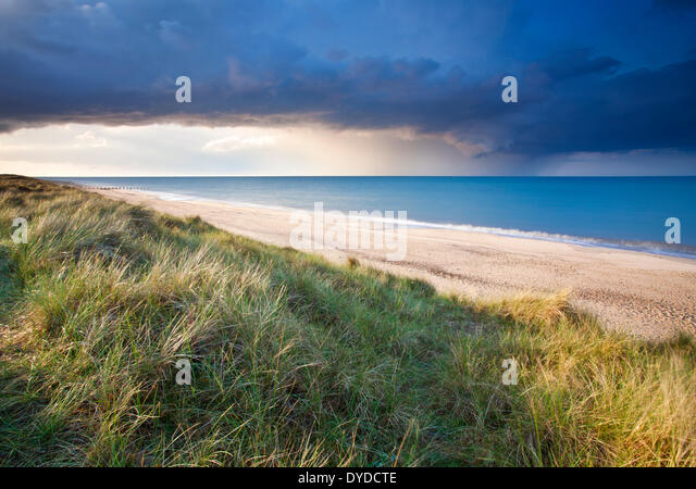 Sand dunes at Horsey and a dramatic summer storm out at sea. - Stock Image