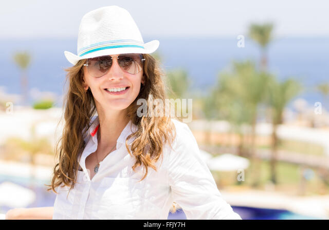 Young european smiling woman in white shirt and hat at the tropical resort. Summer holiday background with happy - Stock Image