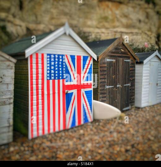 Beach hut painted in the flags of the UK and USA - Stock Image