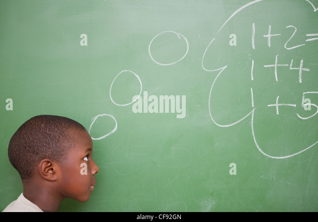 Smart schoolboy thinking about additions - Stock Image