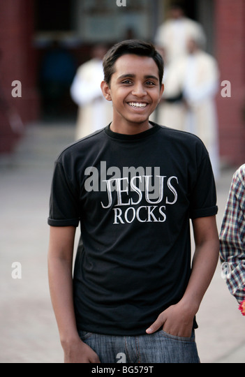 Young christian man in his religious theme shirt printed JESUS ROCKS. Lucknow, India - Stock-Bilder