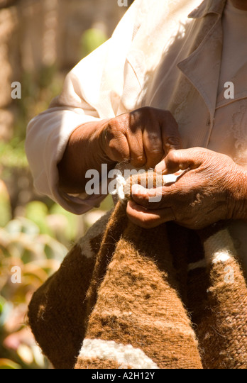 Chile closeup hands of a man sewing traditional blanket - Stock Image