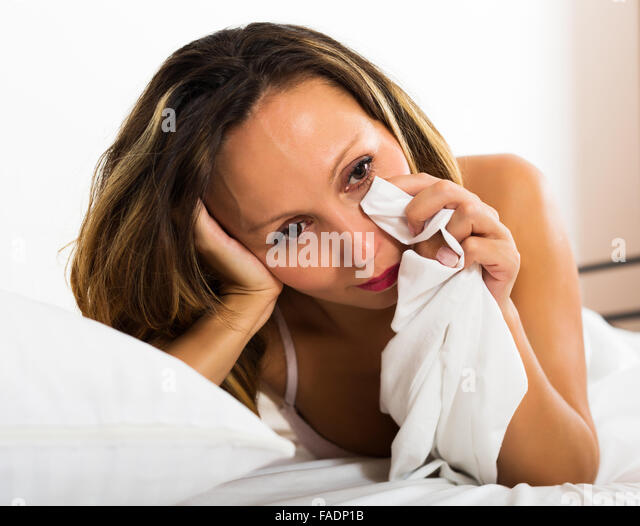 Portrait of thoughtful female with downcast eyes in bed - Stock Image