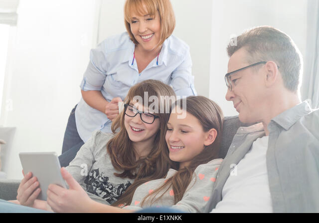 Happy family using tablet PC on sofa at home - Stock-Bilder