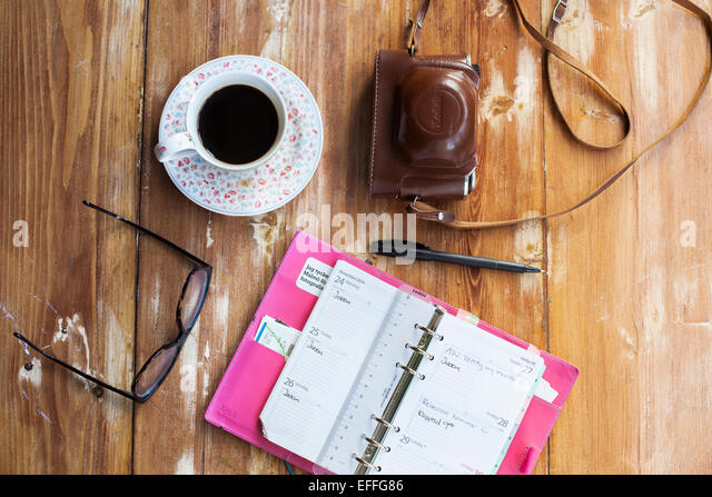 Top view of open diary with glasses, coffee, pen and camera on wooden table - Stock Image