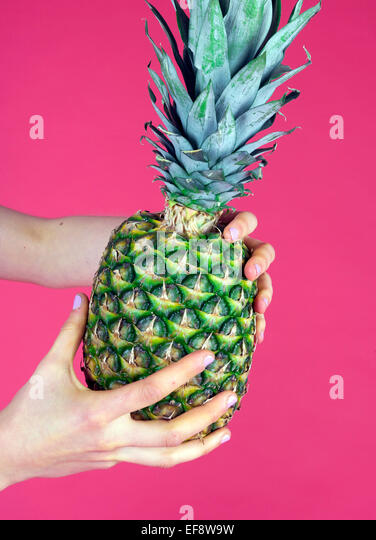 Woman holding pineapple - Stock Image