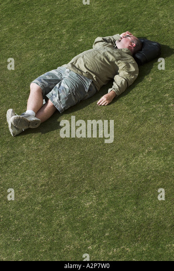 A man sleeping on the grass at the J. Paul Getty Museum in Los Angeles, CA. - Stock Image