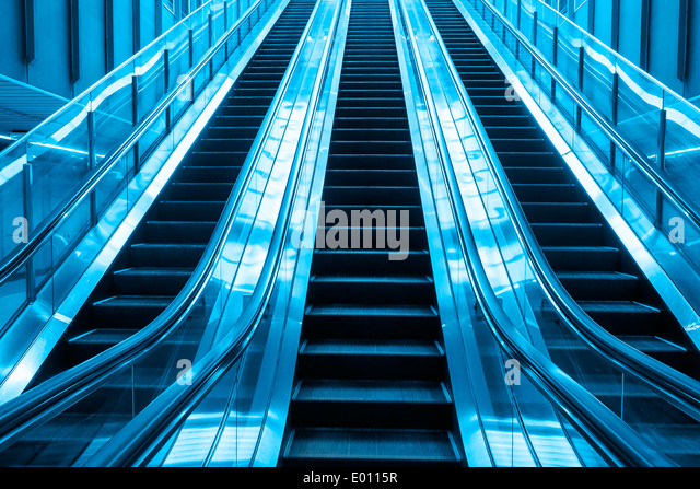 escalator blue two tone color going up stair in building - Stock Image